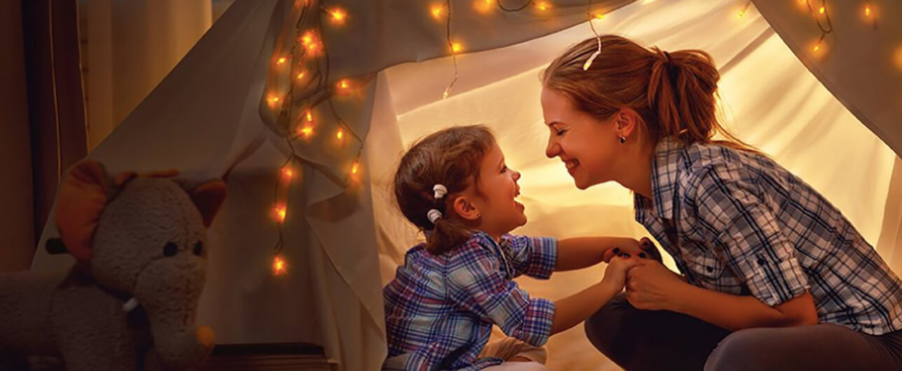happy mother and daughter in an inside tent fort