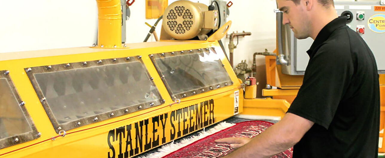 Stanley Steemer employee preparing to feed a rug to a steam cleaner machine