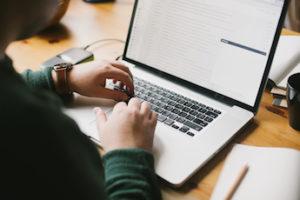 Man Writing an E-Mail on a Laptop