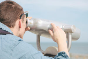 Young Man Using Binoculars in Rockway Beach