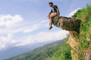 Adveturer man sitting on a rock with his feet dangling on natural landscape. Adventure travel