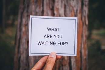 "Hand holding a note card that reads ""What are you waiting for?"" with forest background."
